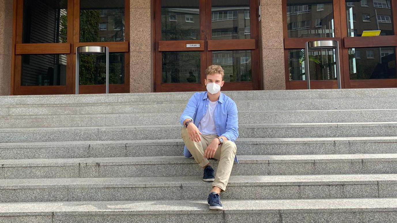 Javier Segovia sentado en las escaleras de entrada del Colegio Mayor Larraona