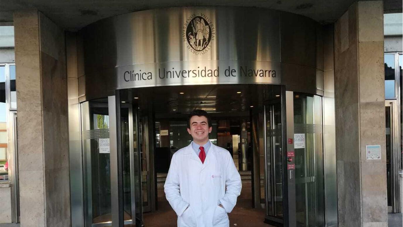 Pablo Nieto con la bata de médico frente a la Clínica Universitaria de Navarra