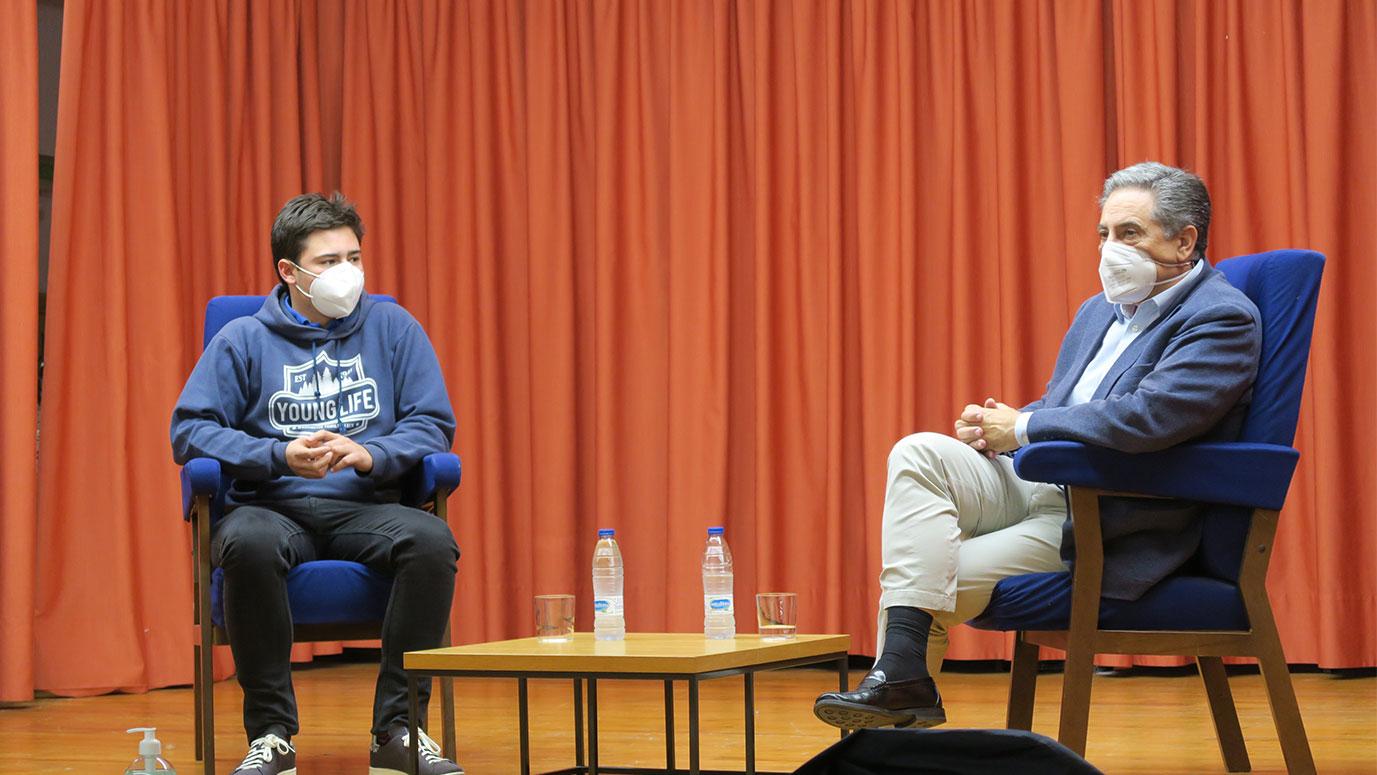 Un joven y un hombre charlando con mascarilla