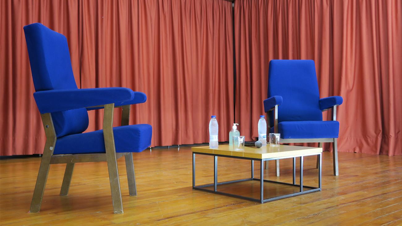 Dos sillas y una mesa en la tarima del Salón de Actos