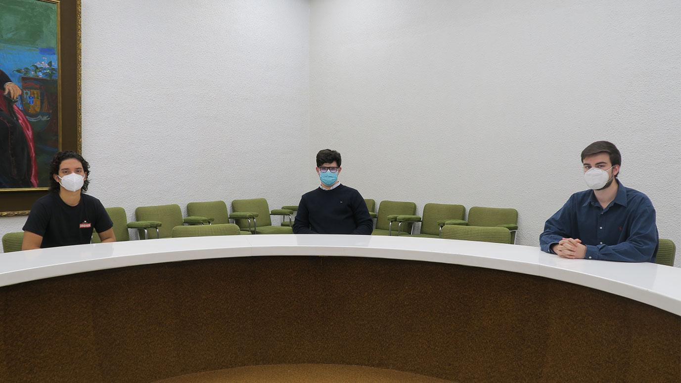 Tres estudiantes con mascarillas sentados en una mesa redonda