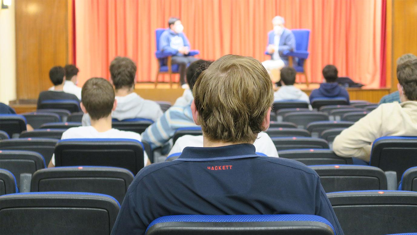Jóvenes de espaldas sentados en un auditorio