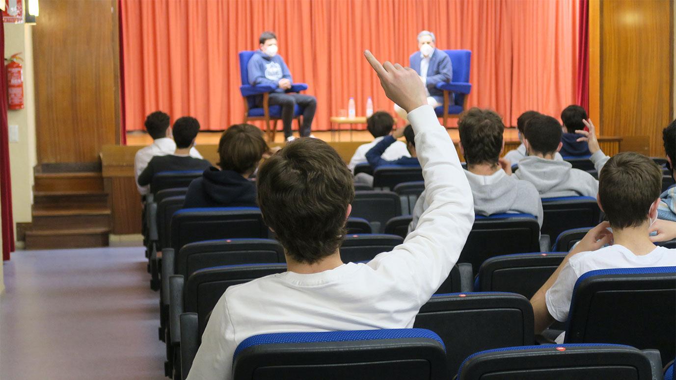 Joven de espaldas levantando la mano