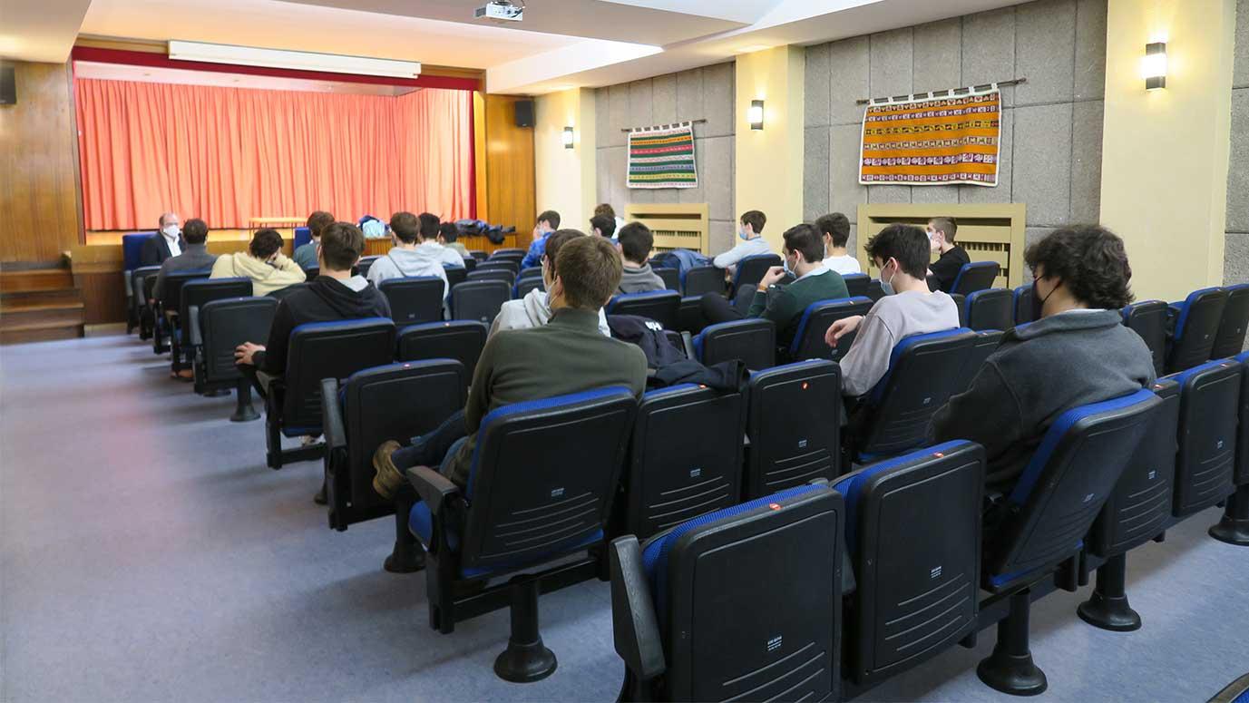 estudiantes sentados en butacas asisten a una charla