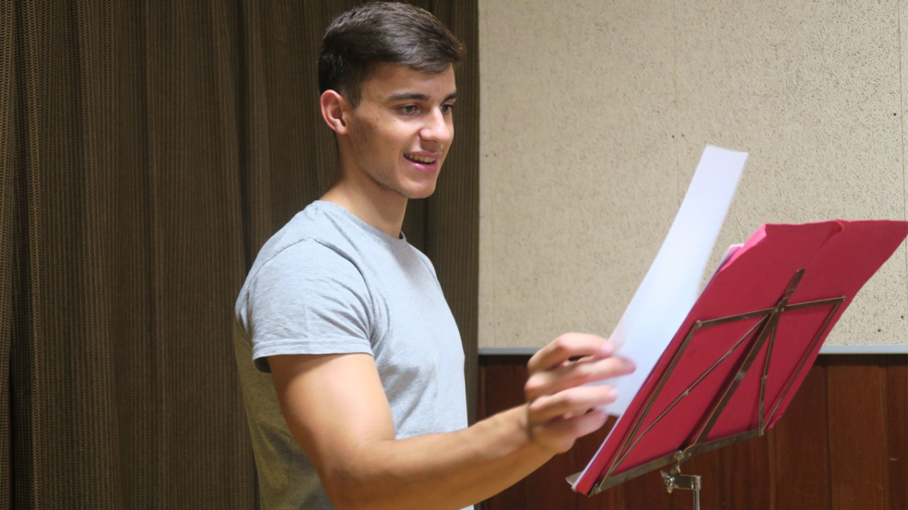 estudiante mirando partitura en sala de música
